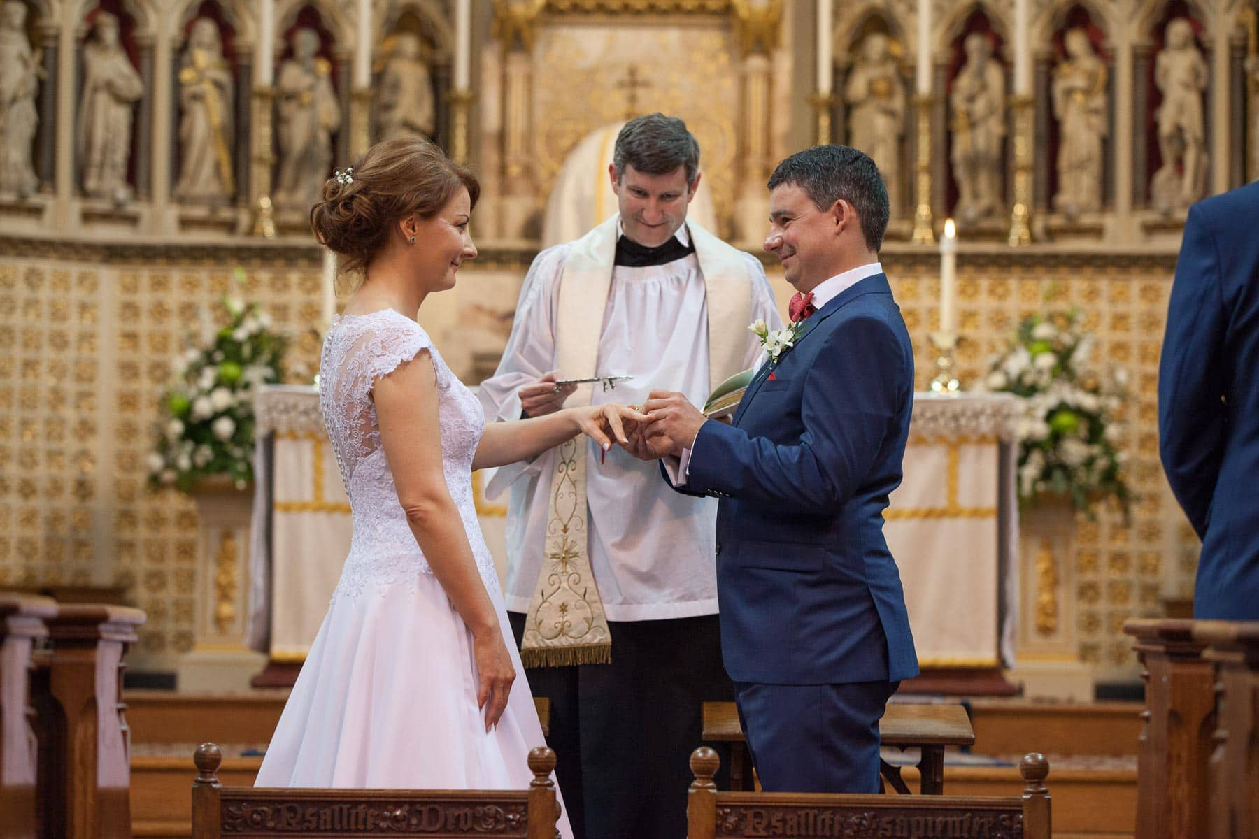 Groom puts ring on bride's finger at church ceremony