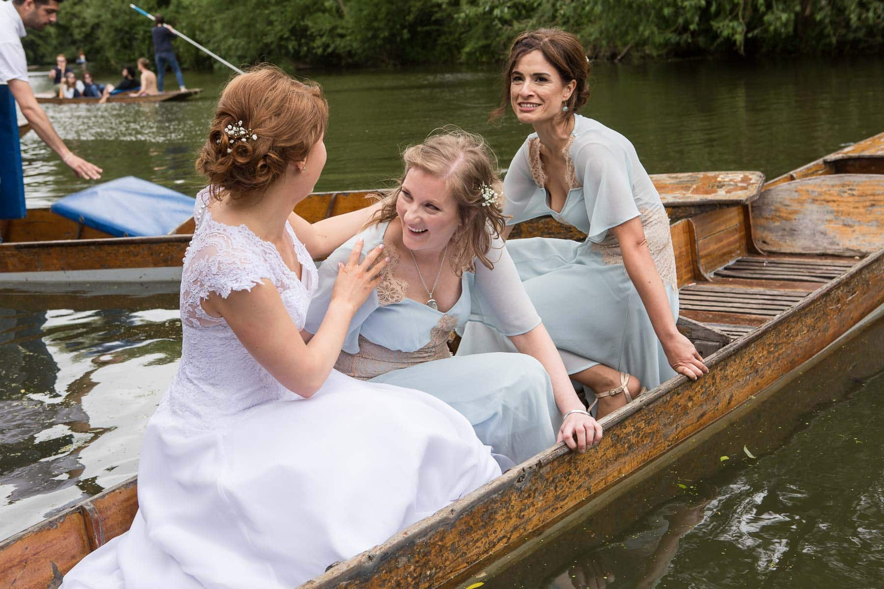 Bride and bridesmaids laugh together in punt