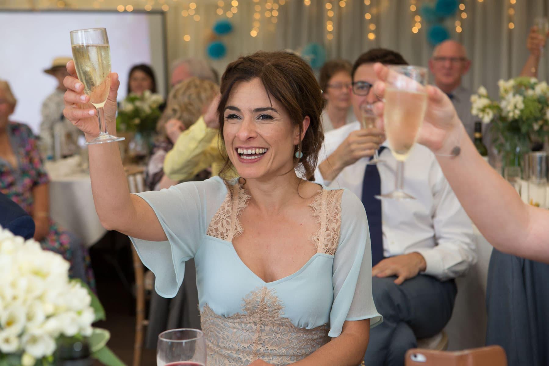 Bridesmaid raises her glass during speeches