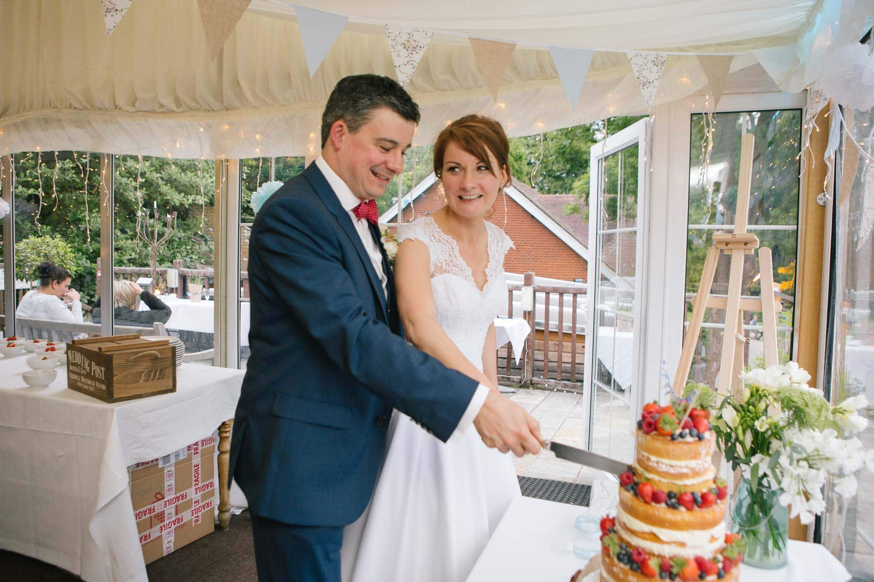 Bride and groom cut their naked wedding cake