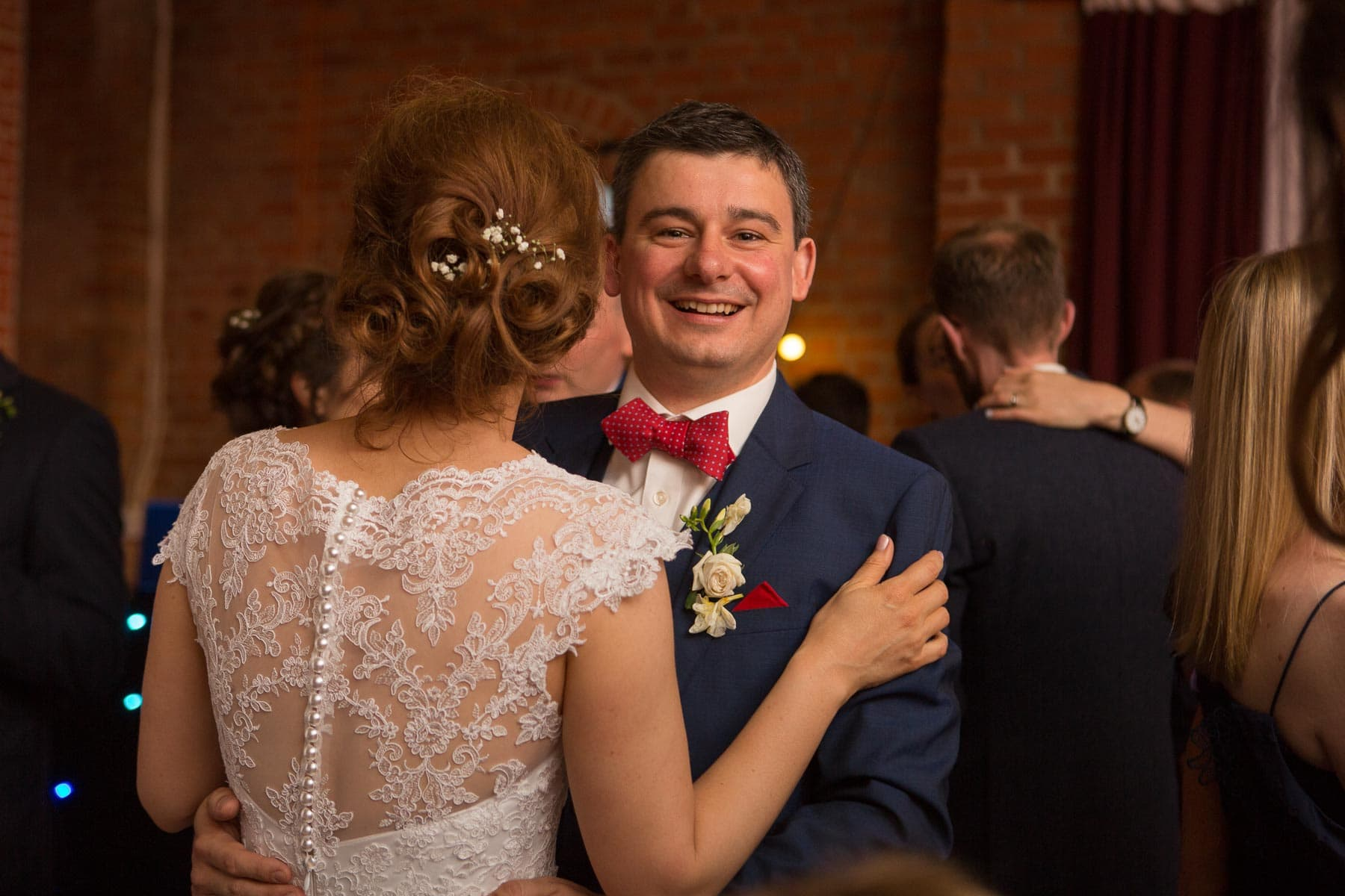 Groom smiles as he holds his bride on the dancefloor