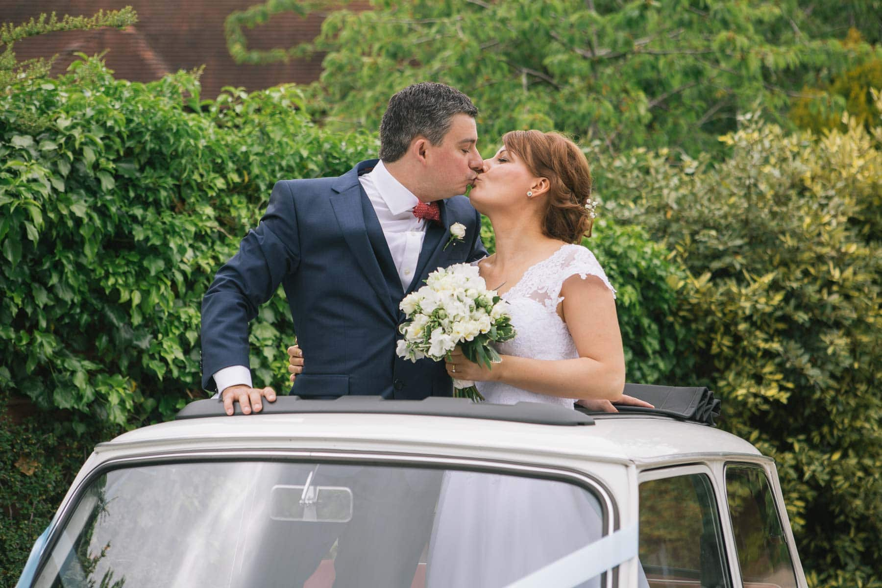 Bride and groom kiss while standing on the seat of their vintage mini