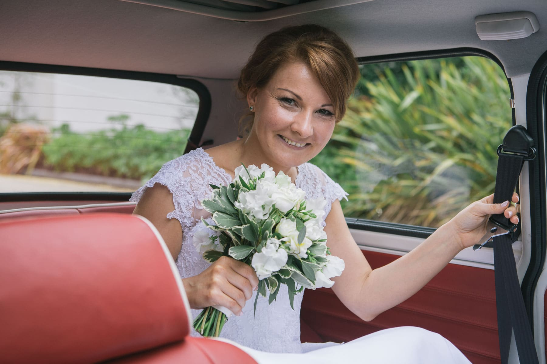 Bride holds bouquet in back seat of vintage mini