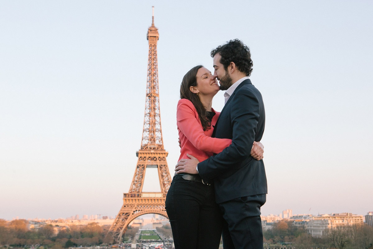Couple kiss in Paris with Eiffel Tower in the background