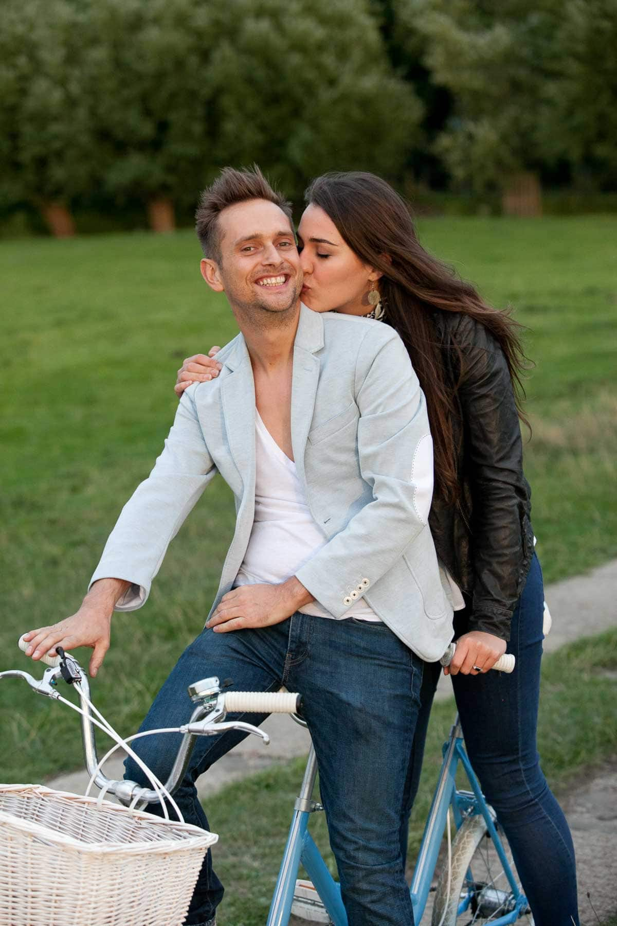 Woman kisses man's cheek while posing on a tandem