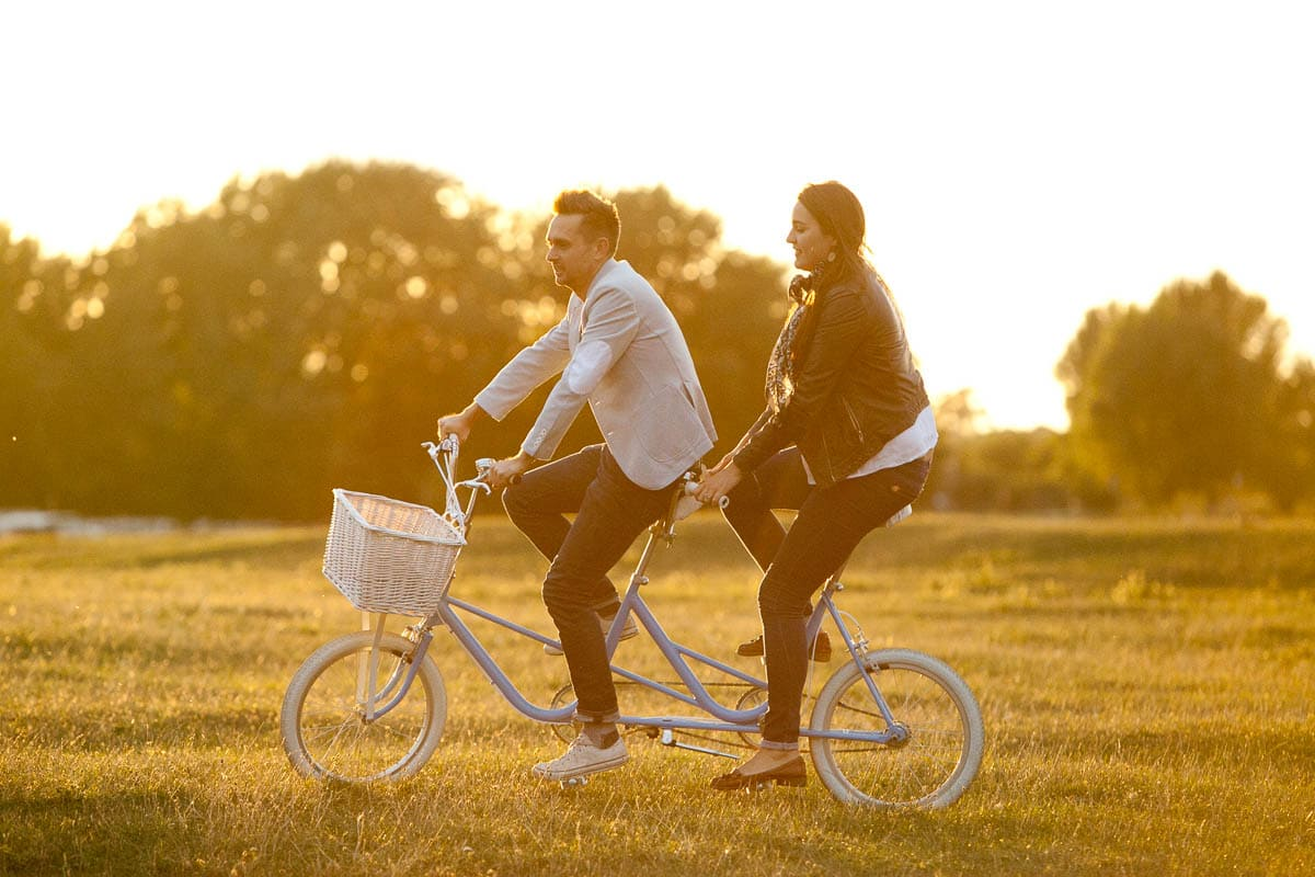 Golden hour shot of couple riding tandem in Port Meadow on their pre-wedding shoot