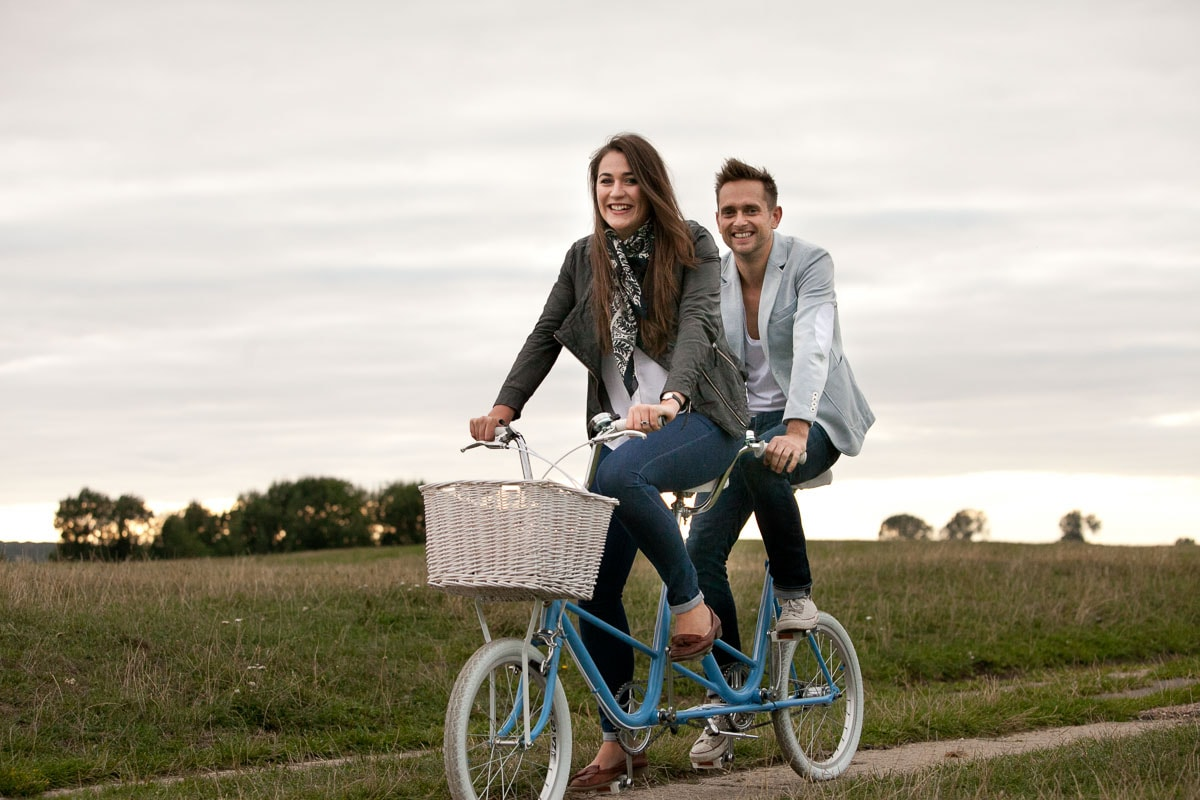 Couple riding tandem in Port Meadow, Oxfordshire at pre-wedding shoot