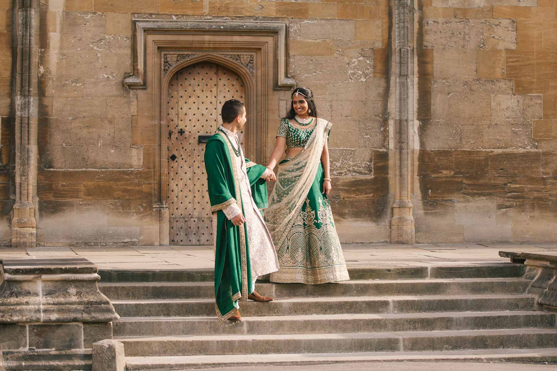 Bride and groom in green and gold Indian dress hold hands on steps of Christchurch college