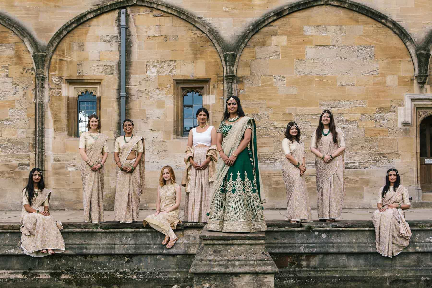 Bride and bridal party on steps of Christchurch college. They wear green and gold saris.