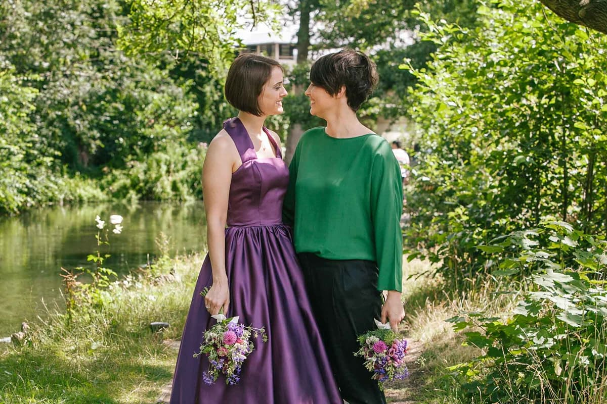 Lesbian brides in purple and green embrace by the river in Oxford