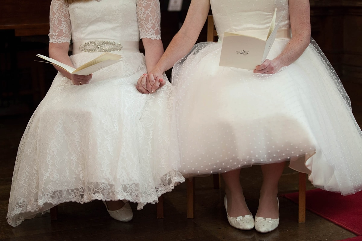 Lesbian brides hold hands during their gay wedding ceremony in Oxford