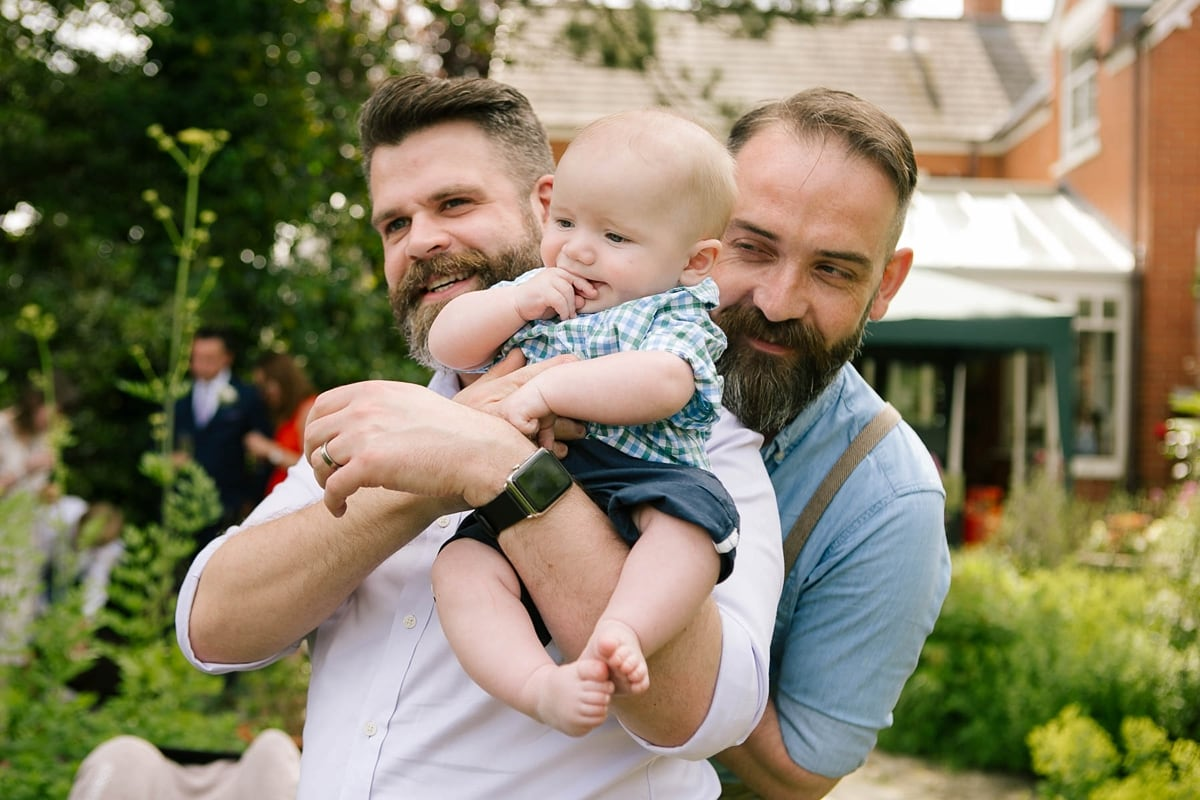 Gay couple with beards play with a baby at a wedding