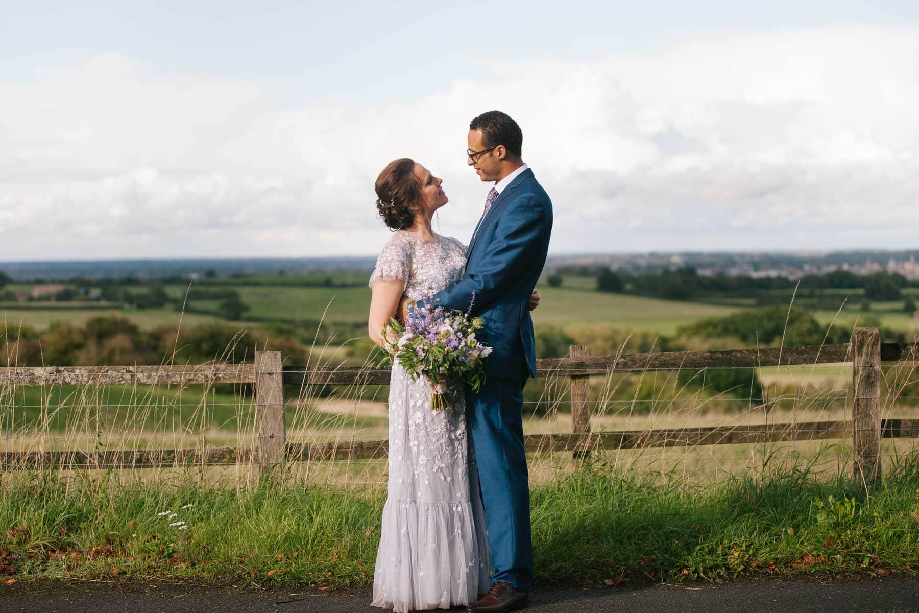 Bride and groom embrace next to fence overlooking Oxfordshire countryside