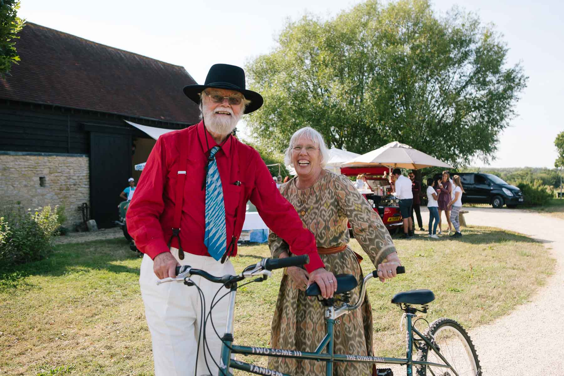 Bride in patterned dress and groom in scarlet shirt pose next to tandem bicycle