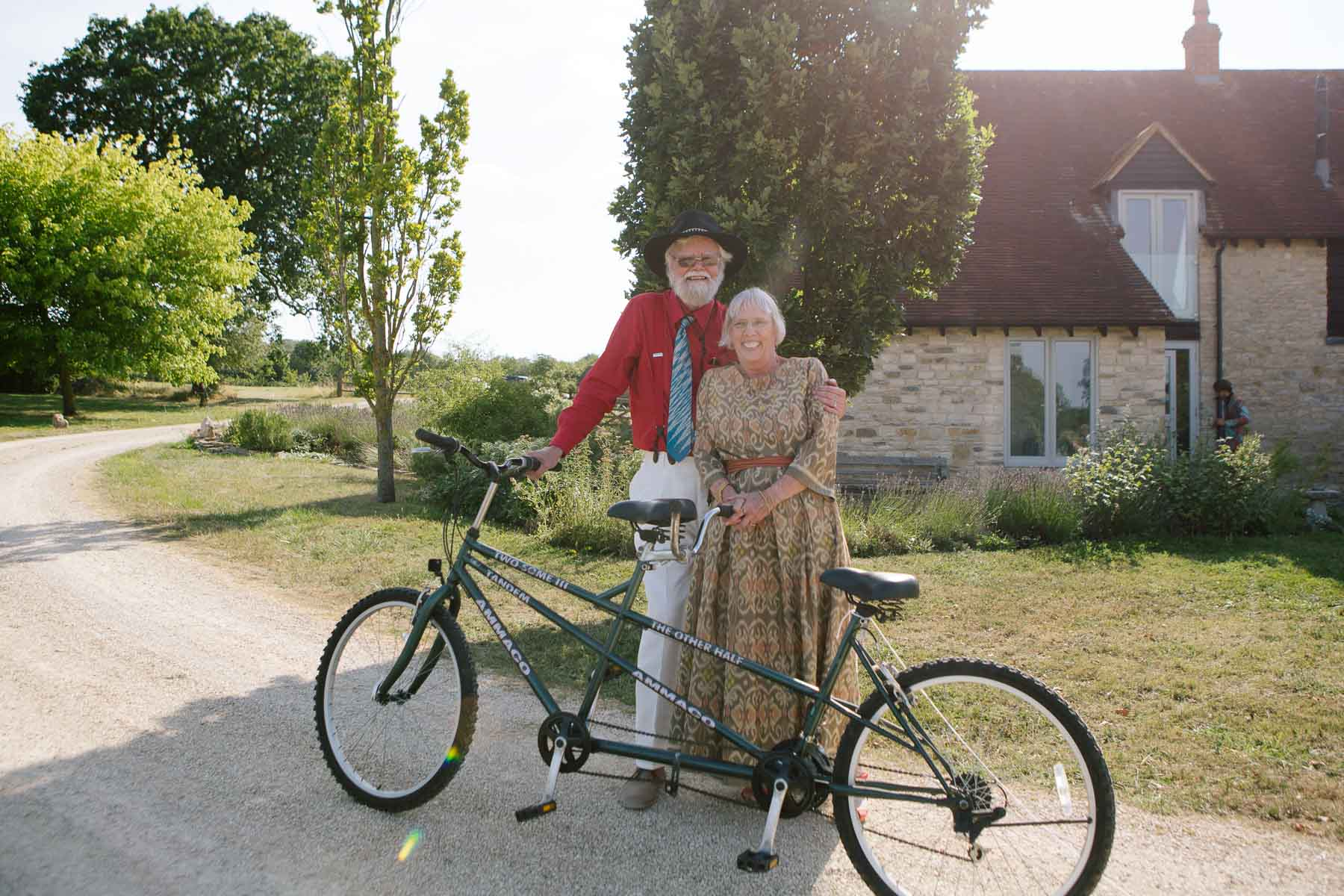 Bride and groom pose next to tandem bicycle