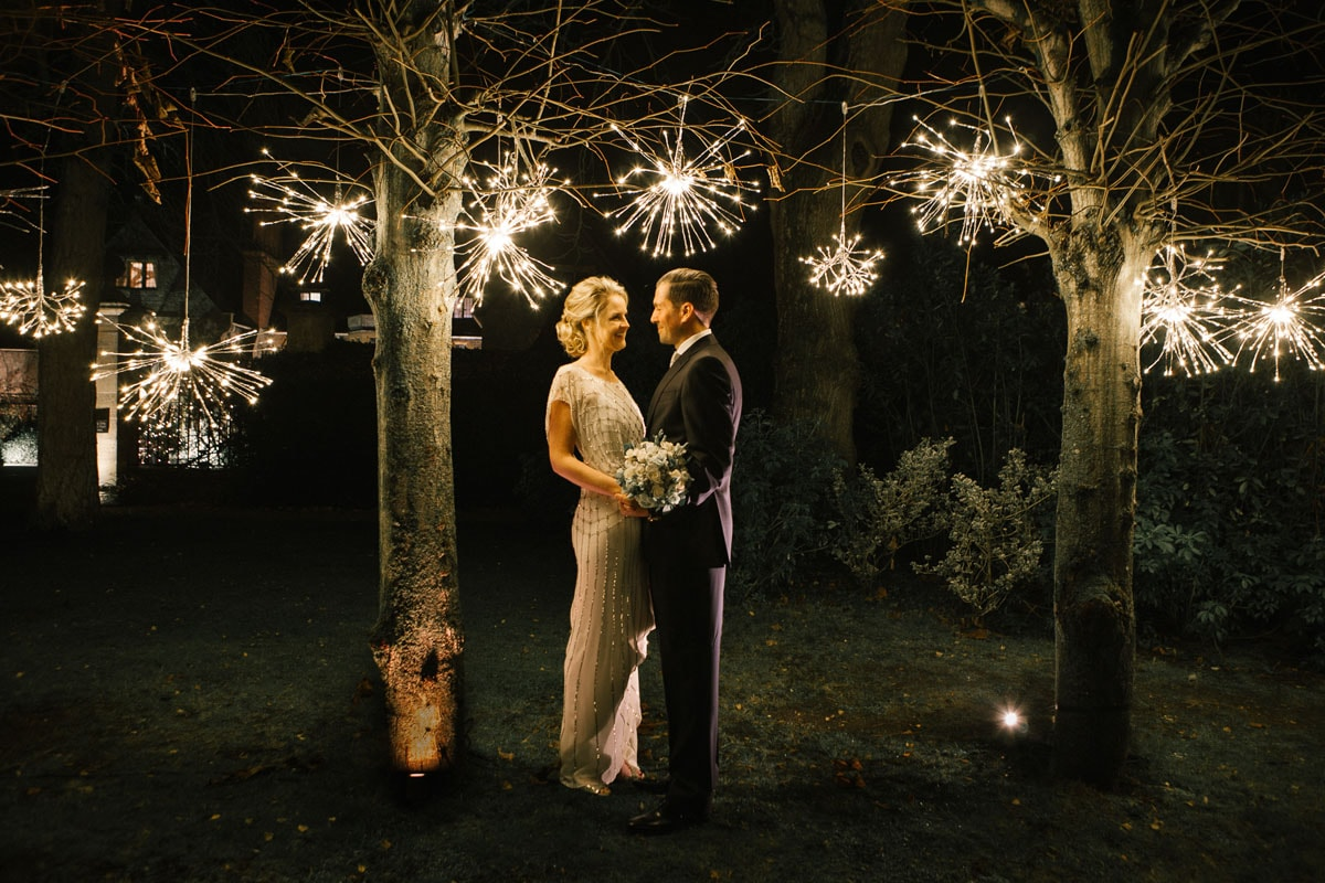 Bride and groom among trees with hanging lanterns