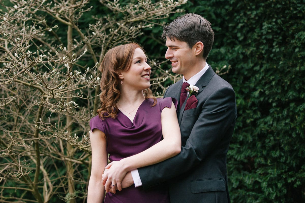Bride and groom couple's shot at winter wedding. Bride wears dress in deep plum colour