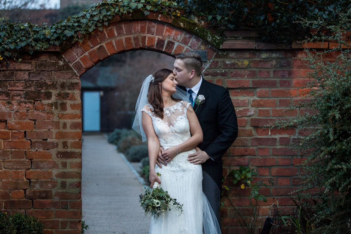 Couple embrace at winter wedding by walled garden
