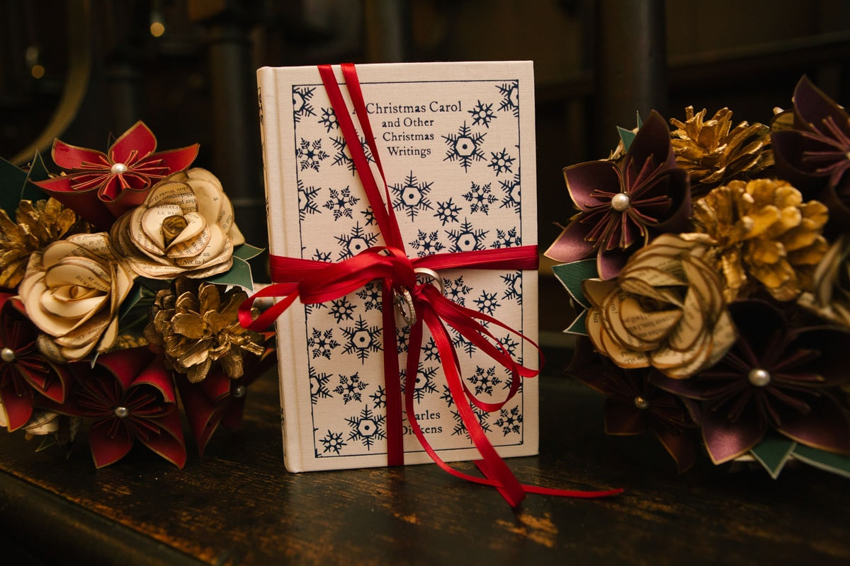 Hardback book of A Christmas Carol tied with red ribbon among paper flowers at a winter wedding