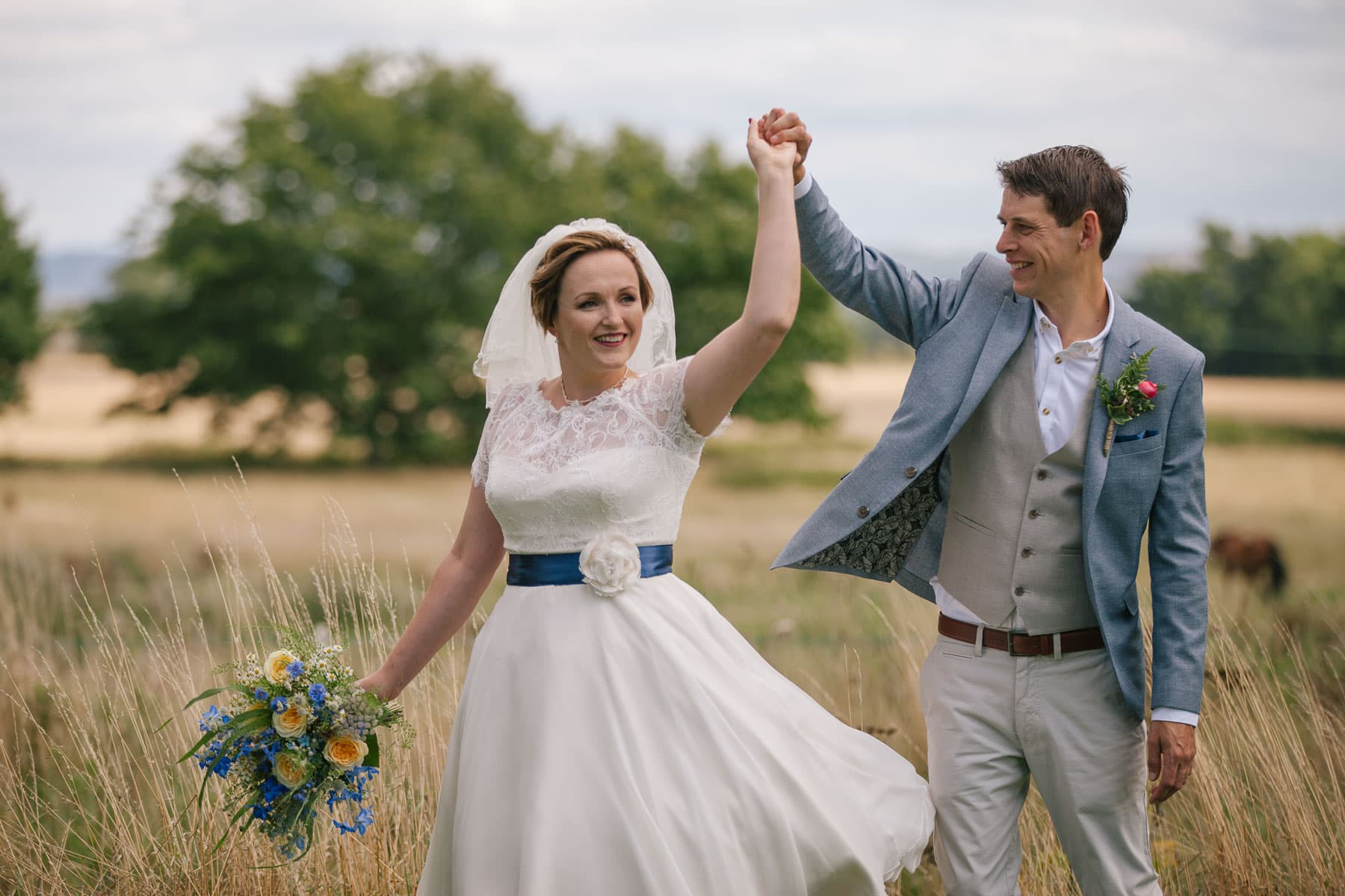Groom in blue suit twirls his bride in a field.