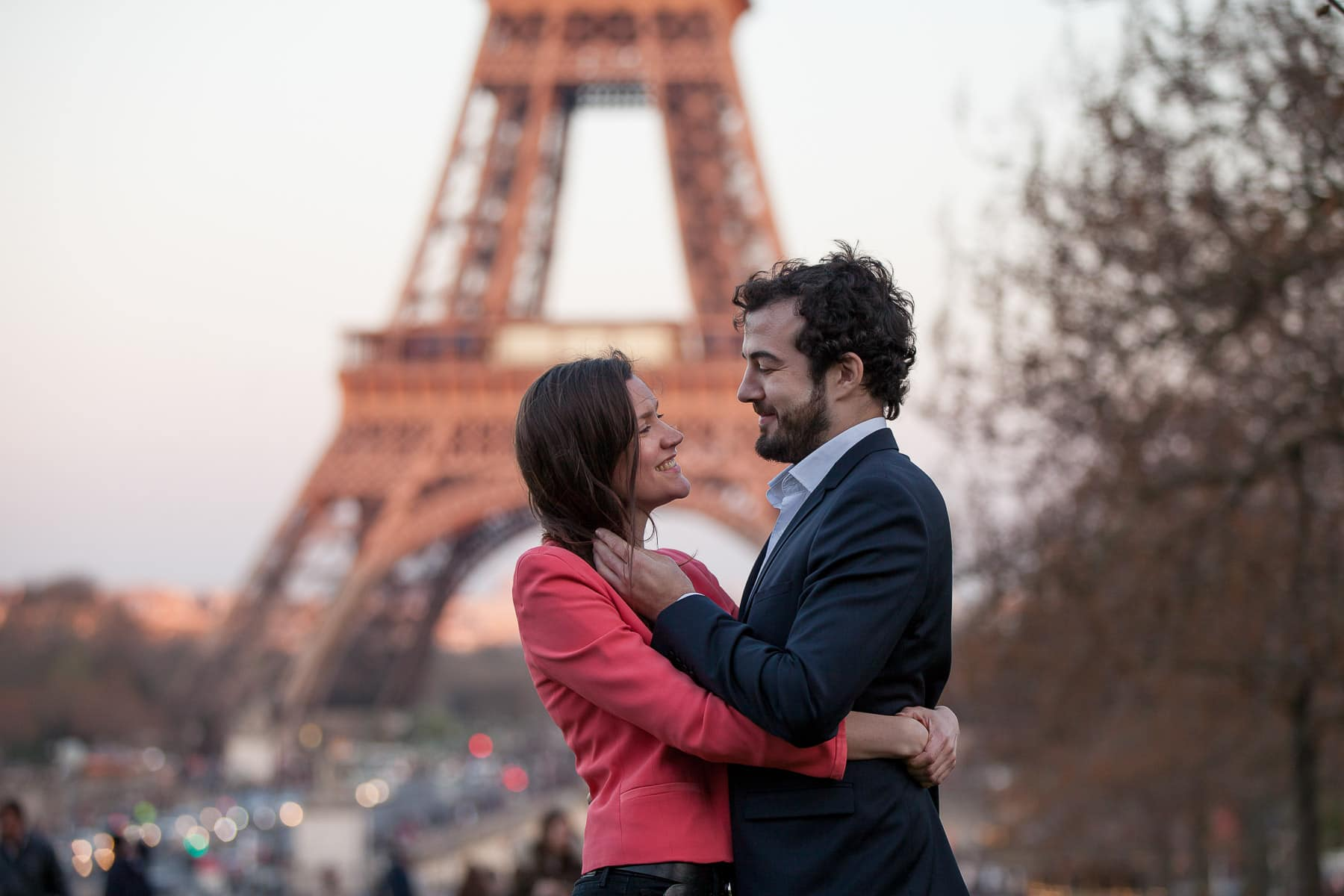 Couple embrace in front of Eiffel Tower