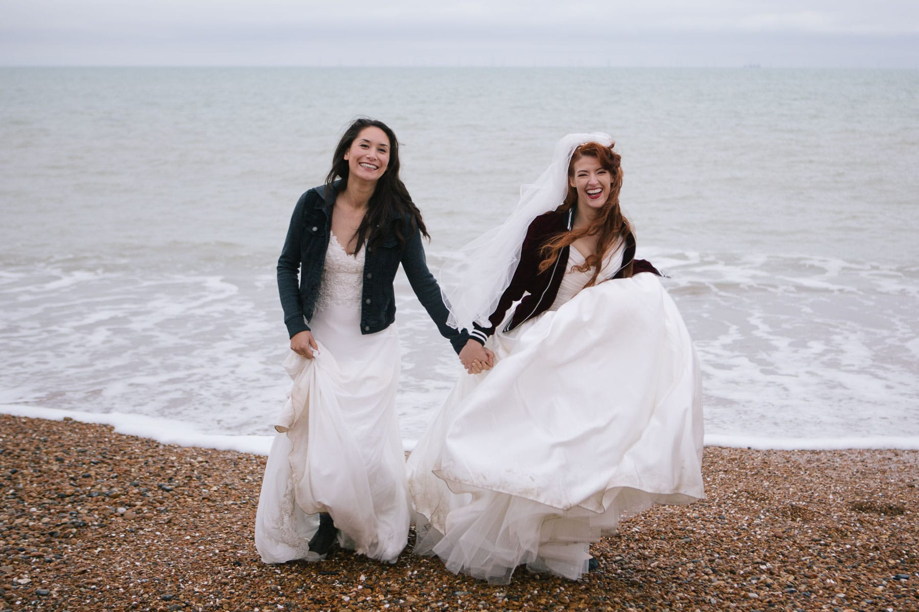 Lesbian brides on Brighton beach wearing gowns and leather jackets