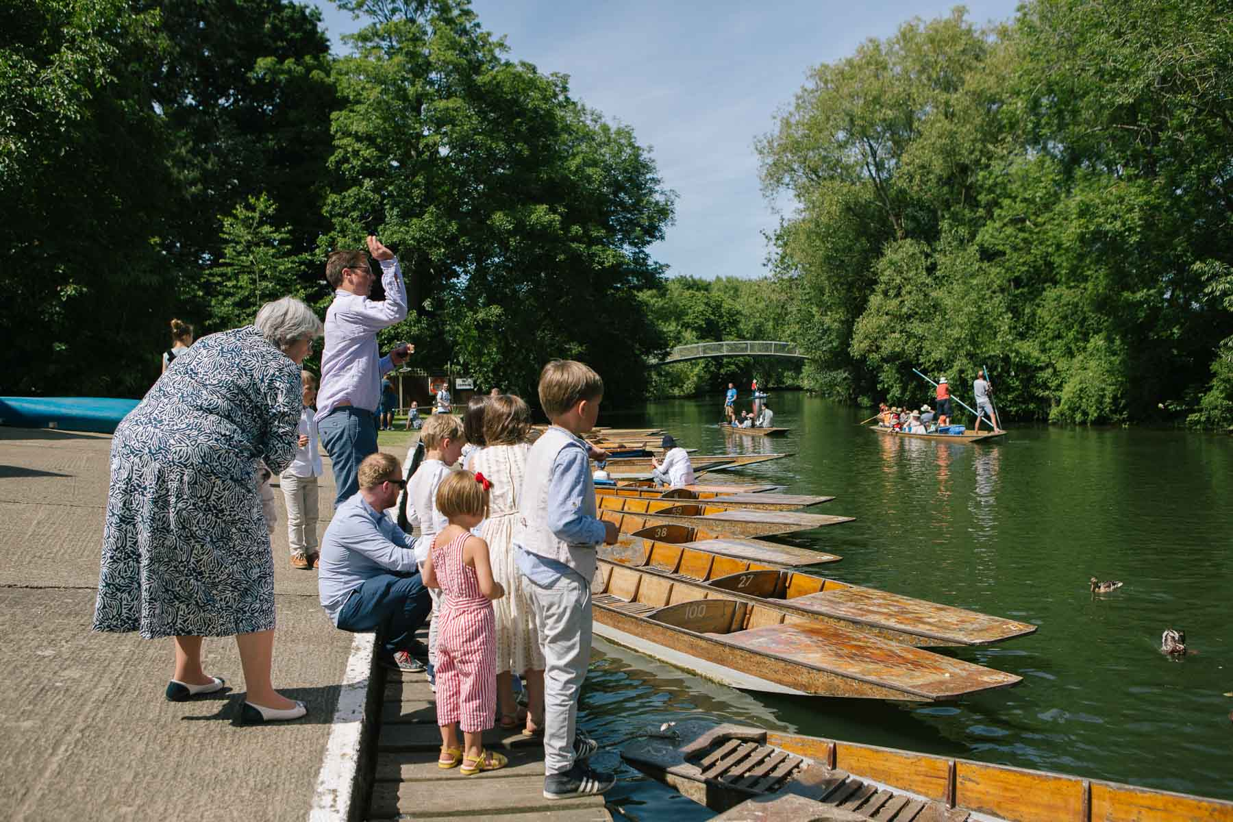 Guests wait for the brides to arrive by punt on the banks of the river in Oxford