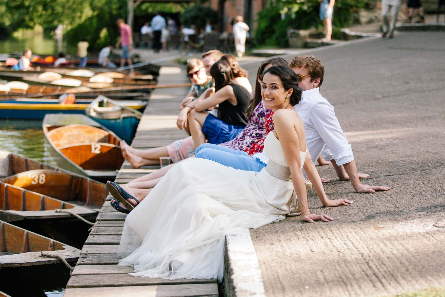 Bride sits on the banks of the river in Oxford