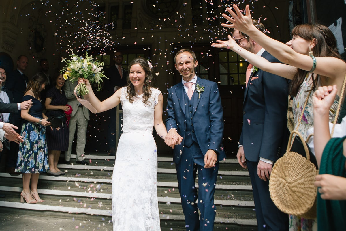 Bride and groom leave Oxford Town Hall. Colourful confetti on steps.