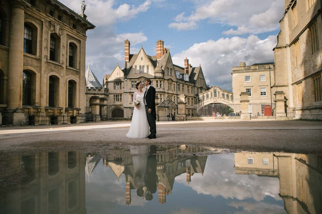 bride and groom in front of the bridge of sighs in Oxford with a reflexion in a puddle