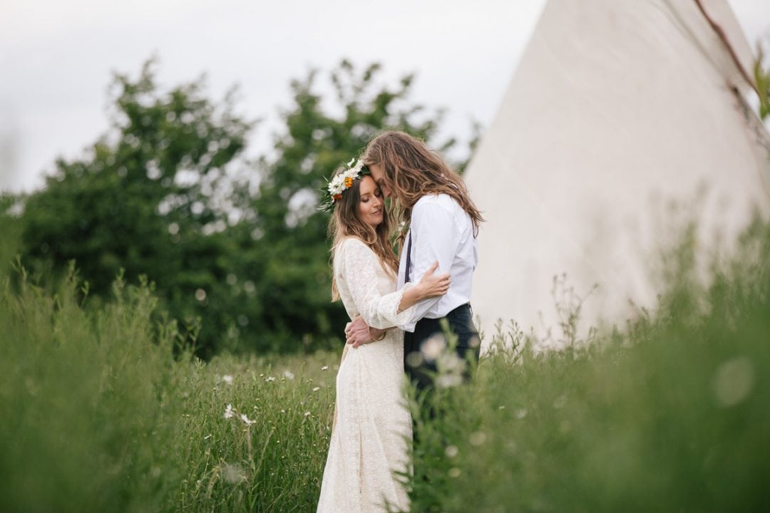 Wedding couple cuddle in front of a tipi
