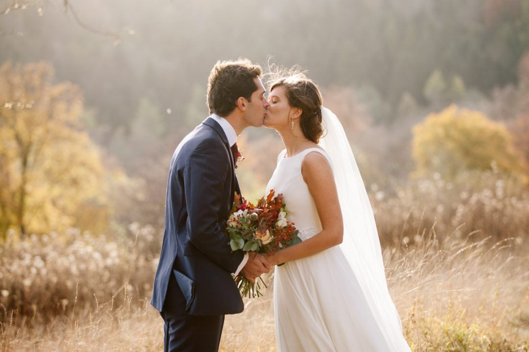 A bride and groom kiss at golden hour.