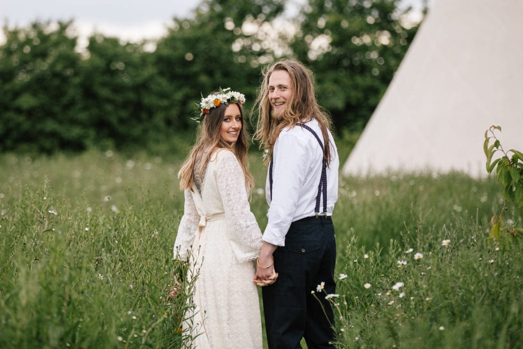 Boho couple in front of a tipi