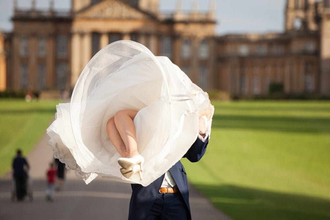Groom lifts bride up at Blenheim Palace