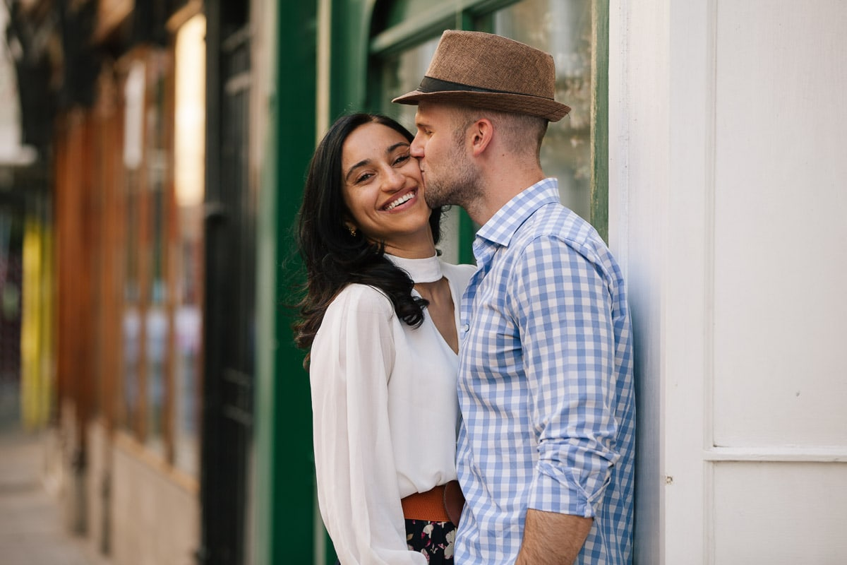 A man kisses a woman while she smiles in front of a painted green shopfront