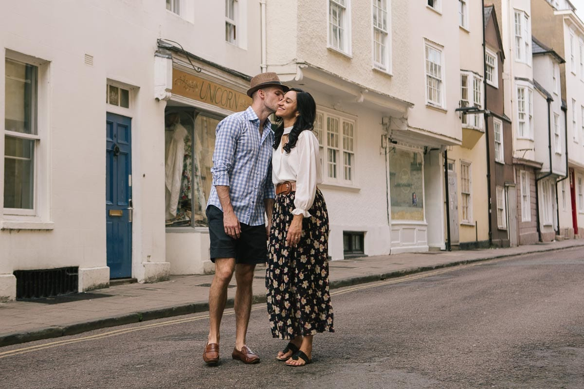 A couple kiss while walking on an Oxford street with the Unicorn shop in the background
