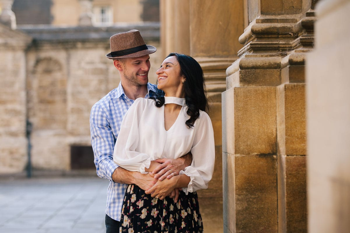 Beautiful couple smile and embrace in front of the Bodleian Library in Oxford